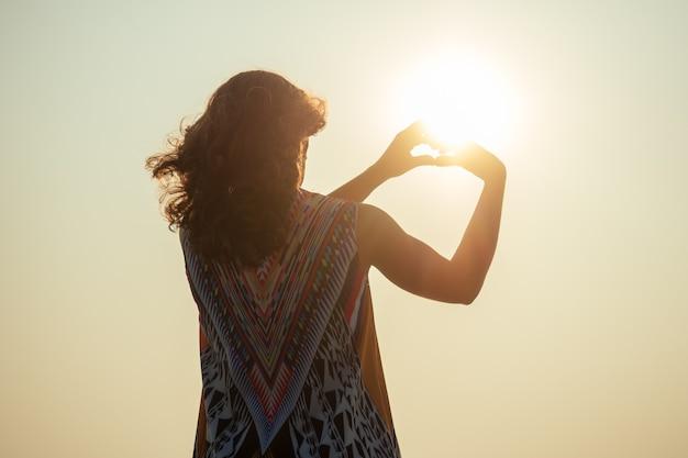 Jeune et heureuse fille posant avec la silhouette des mains du coeur. reconnaissance dans un amour heureux sur la plage en vacances