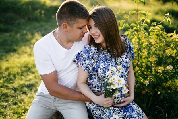 Jeune heureux beau couple amoureux marchant ensemble sur l'herbe et les arbres parc paysage