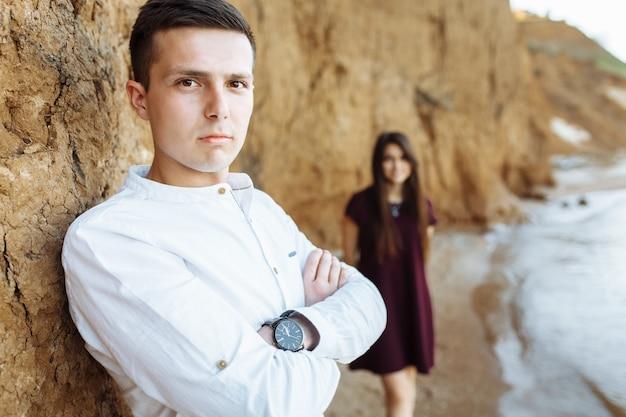 Jeune, heureux, couple d'amoureux, près du mur de sable, sur la mer, posant