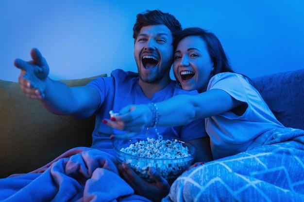 Jeune et heureux couple regardant une émission de télévision comique à la maison