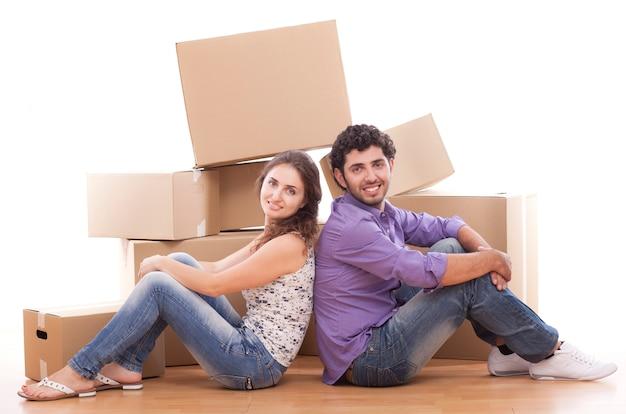 Jeune et heureux couple transportent des boîtes