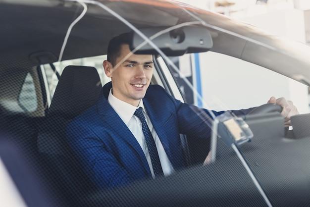 Jeune et heureux homme d'affaires assis dans une nouvelle voiture dans la salle d'exposition