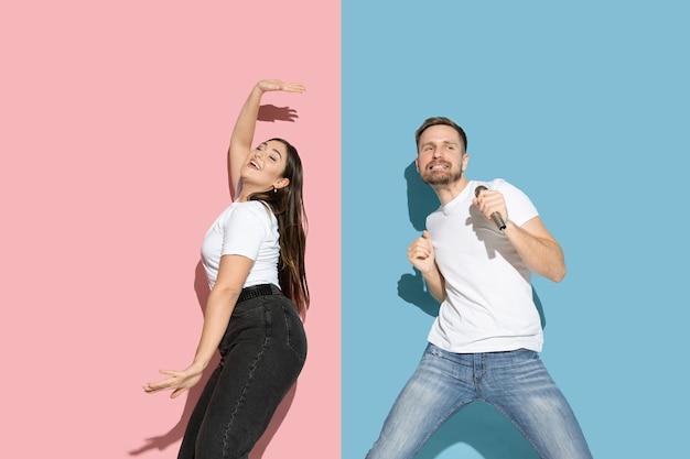 Jeune et heureux homme et femme dans des vêtements décontractés sur un mur bicolore rose, bleu, chant et danse