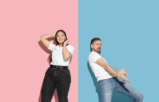 Jeune et heureux homme et femme dans des vêtements décontractés sur un mur bicolore rose, bleu, danse