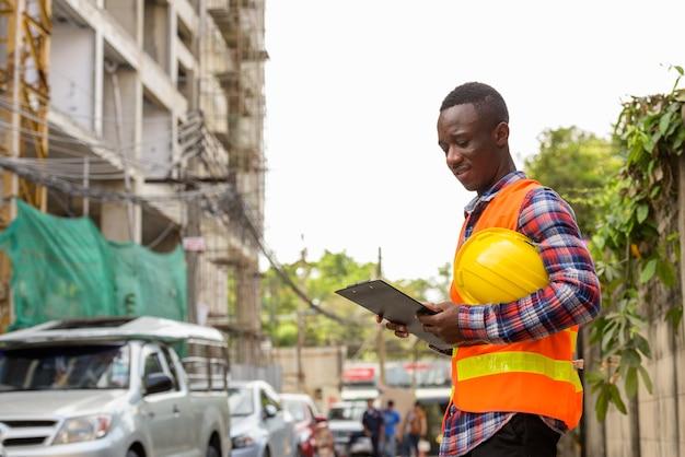 Jeune, heureux, noir, homme africain, ouvrier construction, sourire
