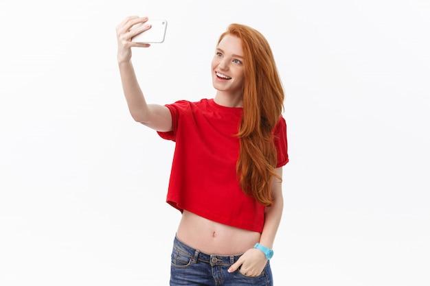 Jeune, heureux, roux, femme, isolé, sur, mur blanc, fond, confection, selfie, regarder appareil-photo