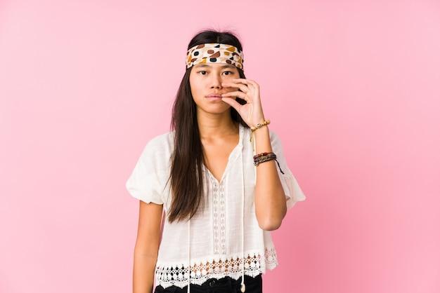 Jeune hippie chinois isolé avec les doigts sur les lèvres gardant un secret.