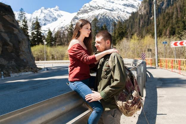 Jeune hipster beau couple amoureux, assis à la route