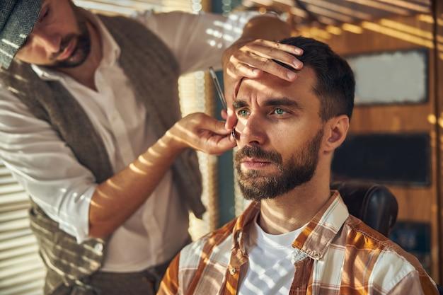 Jeune hipster brune à l'air sérieux tout en restant assis et en se rasant chez un coiffeur