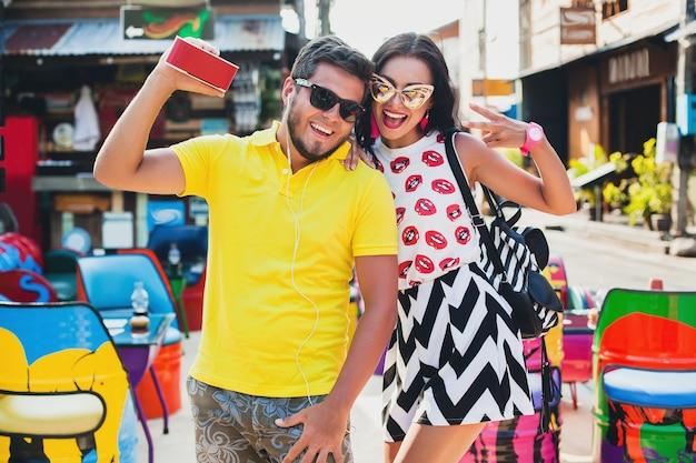 Jeune hipster élégant beau couple assis au café coloré, flirty, tenue de mode, tenue à la mode, lunettes de soleil, vacances tropicales, romance de vacances, lune de miel, souriant, heureux, écoute de la musique