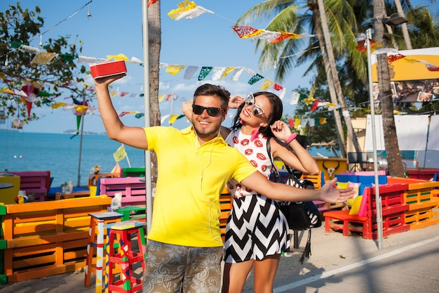 Jeune hipster élégant beau couple en vacances d'été en thaïlande, flirty, tenue tendance de la mode, lunettes de soleil, romance tropicale, souriant, heureux, écoute de la musique, ambiance de fête, café de plage