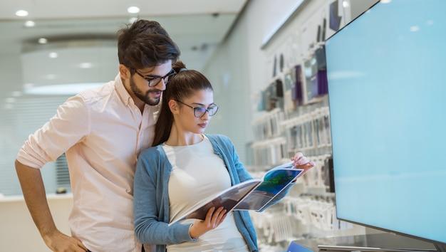 Jeune hipster élégant couple curieux lecture spécification devant la grande télévision à écran plat dans le magasin de technologie.