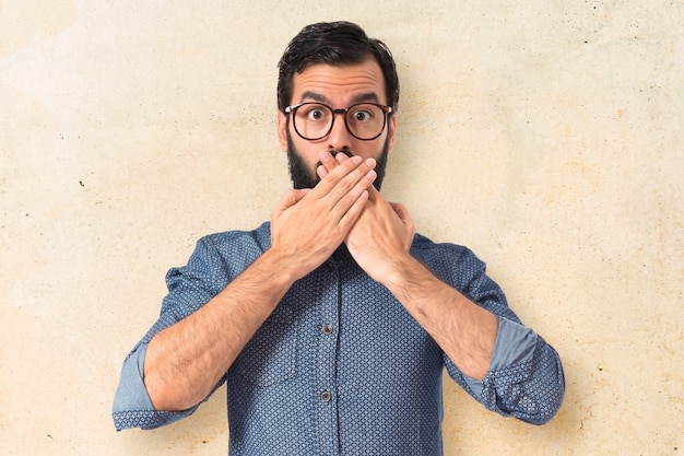Jeune hipster homme faisant un geste de surprise