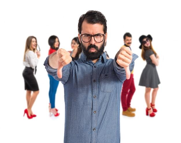 Jeune hipster homme faisant mauvais signal