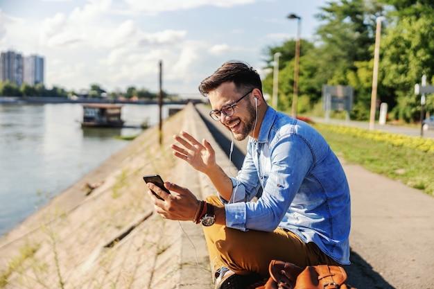 Jeune hipster mal rasé souriant assis à l'extérieur au bord de la rivière et ayant un appel vidéo avec des amis.