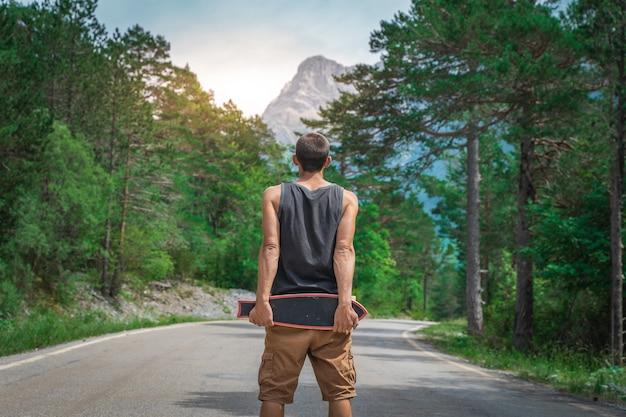 Jeune hipster tenant un longboard cool à la main