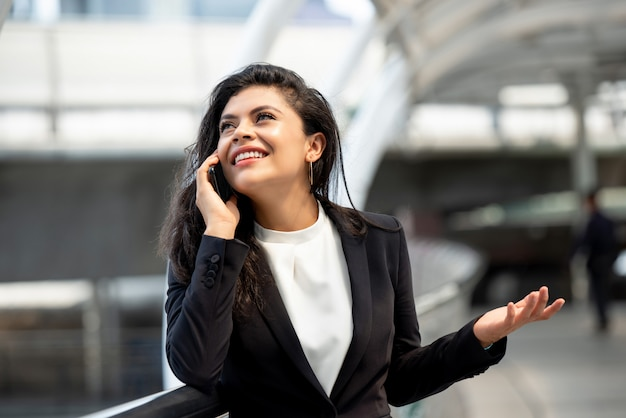 Jeune, hispanique, femme affaires, conversation, sur, téléphone portable, dehors