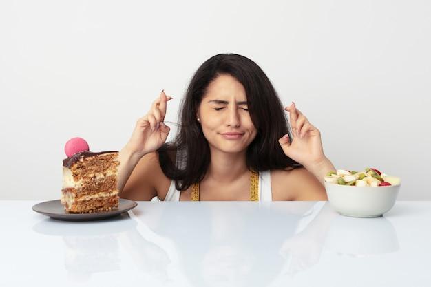 Jeune, hispanique, femme, choisir, gâteau, fruit, croisement, doigts, avoir, chance