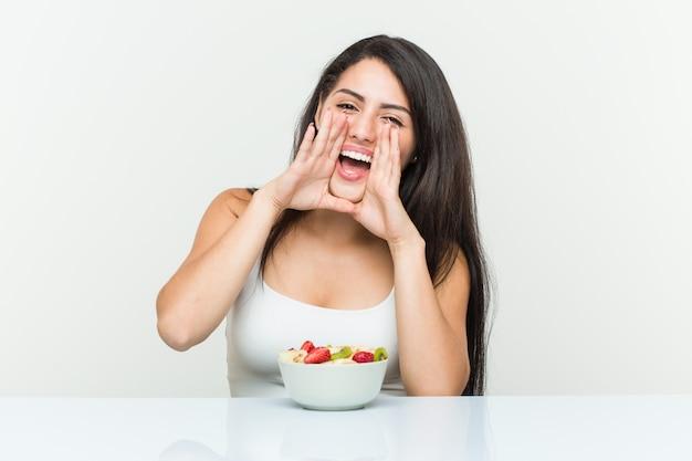 Jeune, hispanique, femme, manger, fruit, bol, cris, excité, devant