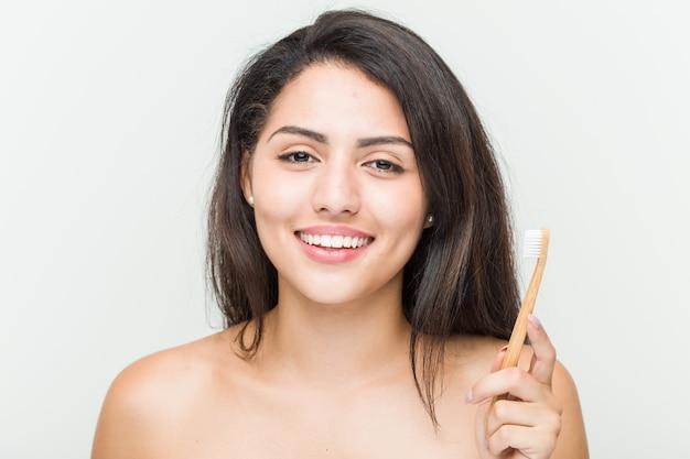 Jeune, hispanique, femme, tenue, brosse dents, heureux, sourire, gai