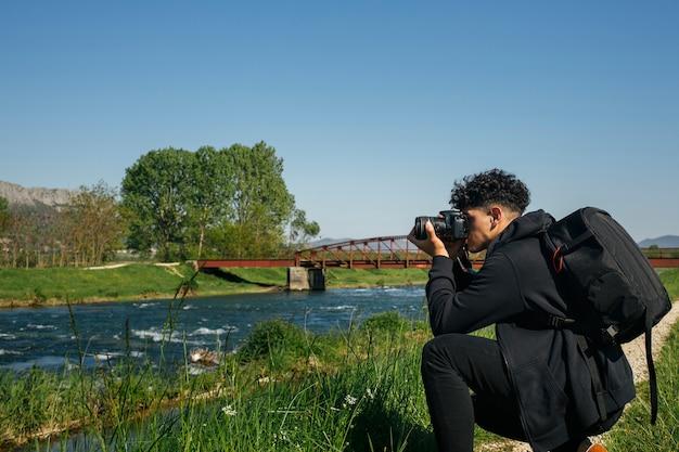 Jeune homme accroupi prenant une photo de la rivière qui coule