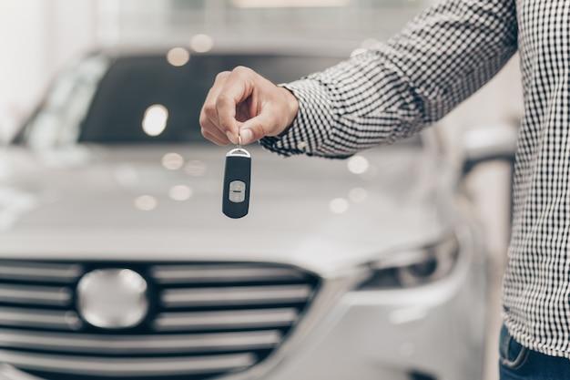 Jeune homme achète une voiture neuve chez le concessionnaire