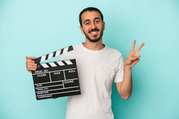 Jeune homme acteur caucasien tenant un clap isolé sur fond bleu joyeux et insouciant montrant un symbole de paix avec les doigts.