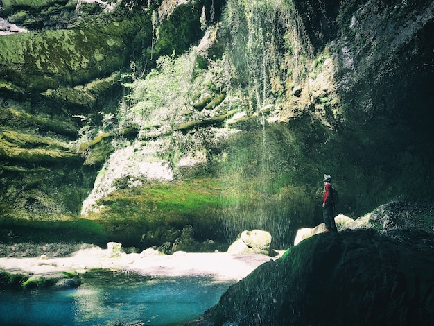 Jeune homme actif debout sur la falaise et levant la cascade