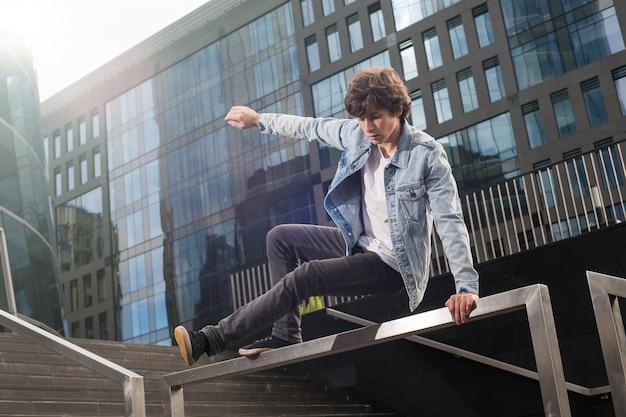 Jeune homme actif faisant du parkour extrême et des cascades dans la ville