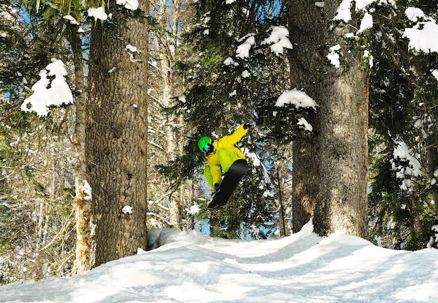 Jeune homme actif sautant sur snowboard à fond de bois