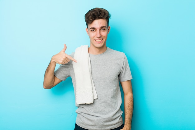 Jeune homme adolescent fitness, pointant à la main vers un espace de copie de chemise, fier et confiant