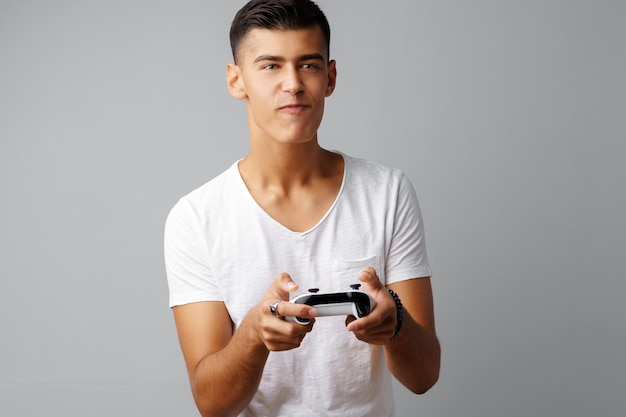 Jeune homme adolescent jouant avec une manette de jeu sur un fond gris