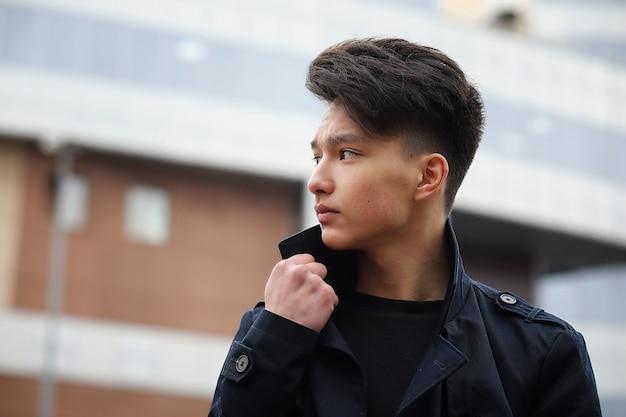 Jeune homme adulte asiatique dans la rue se présentant à la caméra