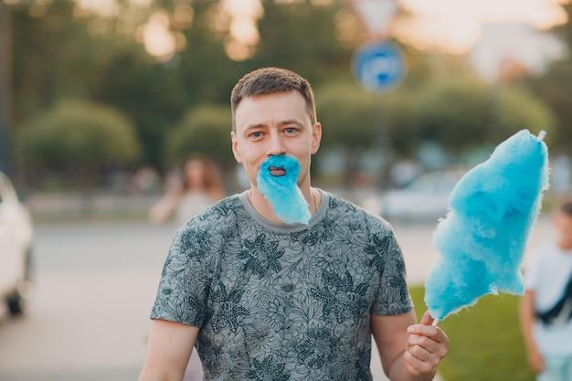 Jeune homme adulte avec barbe en barbe à papa bleue.