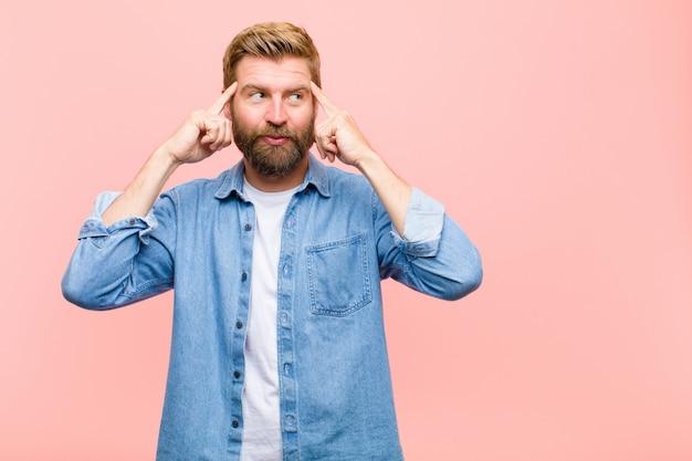 Jeune homme adulte blond, confus ou doutant, se concentrant sur une idée