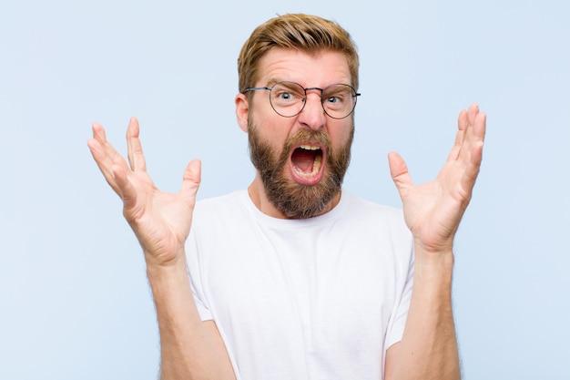 Jeune homme adulte blond criant avec les mains en l'air, se sentant furieux, frustré, stressé et contrarié