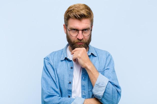 Jeune homme adulte blond à la recherche de sérieux confus, incertain et réfléchi doutant parmi les options ou les choix
