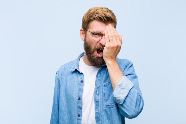 Jeune homme adulte blond à la recherche de sommeil, s'ennuie et bâille, avec un mal de tête et une main couvrant la moitié du visage