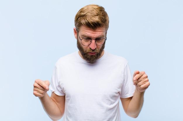 Jeune homme adulte blond se sentant choqué, bouche bée et émerveillé, regardant et pointant vers le bas dans l'incrédulité et la surprise