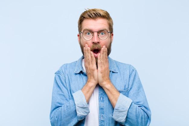 Jeune homme adulte blond se sentant choqué et effrayé, l'air terrifié par la bouche ouverte et les mains sur les joues