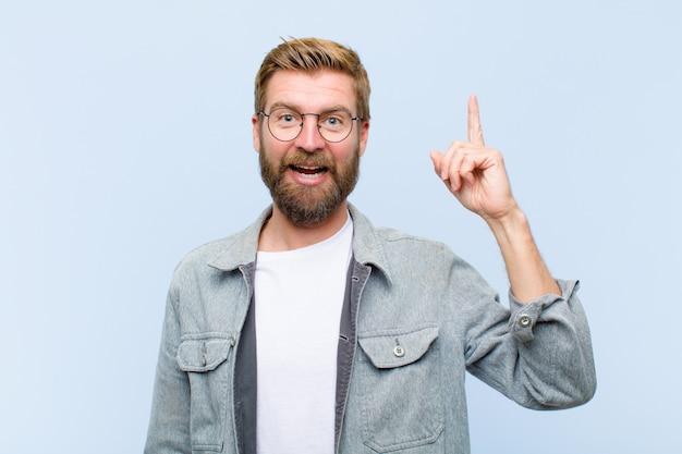 Jeune homme adulte blond se sentant comme un génie heureux et excité après avoir réalisé une idée, levant gaiement le doigt, eureka!