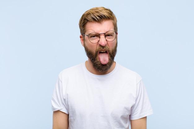 Jeune homme adulte blond se sentant dégoûté et irrité, tire la langue, n'aimant pas quelque chose de méchant et dégueulasse