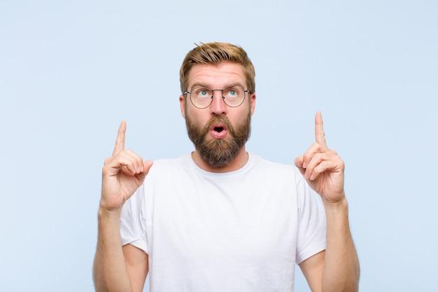 Jeune homme adulte blond se sentant émerveillé et bouche bée pointant vers le haut avec un regard choqué et surpris