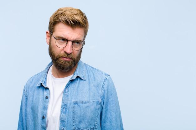 Jeune homme adulte blond se sentant triste, contrarié ou en colère et regardant de côté avec une attitude négative, fronçant les sourcils en désaccord