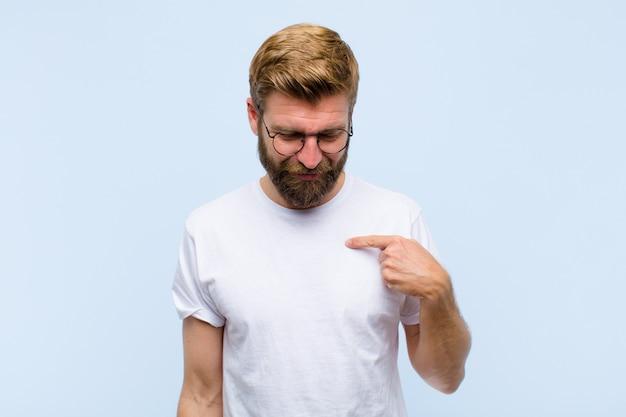 Jeune homme adulte blond souriant avec gaieté et désinvolture, regardant vers le bas et pointant vers la poitrine