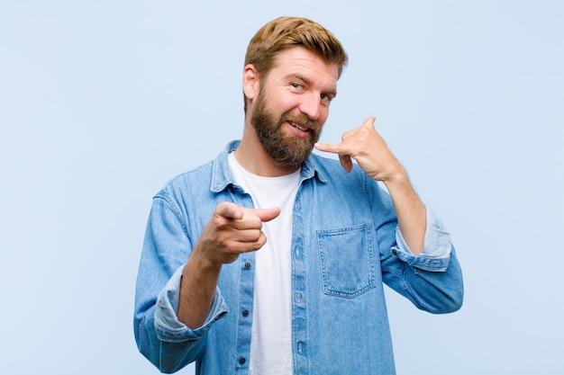 Jeune homme adulte blond souriant joyeusement et pointant tout en faisant un appel vous gestes plus tard, parler au téléphone