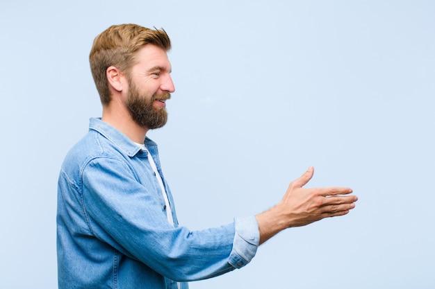 Jeune homme adulte blond souriant, vous saluant et vous offrant une poignée de main pour conclure un accord fructueux