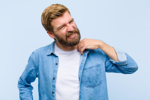 Jeune homme adulte blond, stressé, anxieux, fatigué et frustré, tirant le col de la chemise, semblant frustré par le problème