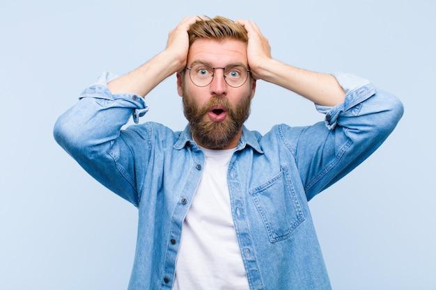Jeune homme adulte blonde semblant excitée et surprise, bouche bée avec les deux mains sur la tête, se sentir comme un gagnant chanceux