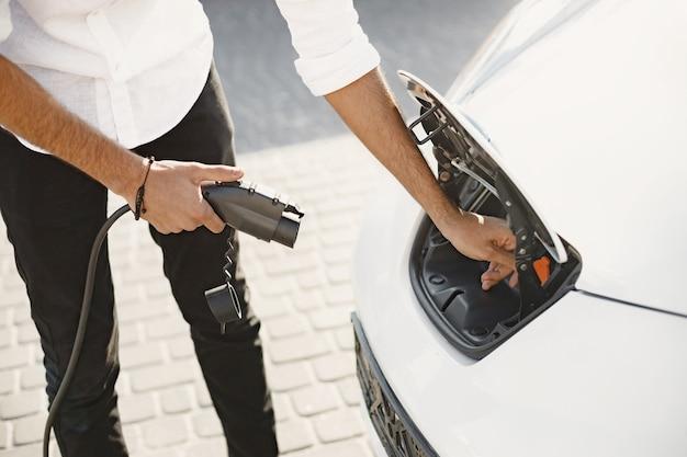Jeune homme adulte chargeant sa voiture électrique dans la ville. concept de voiture électrique écologique.